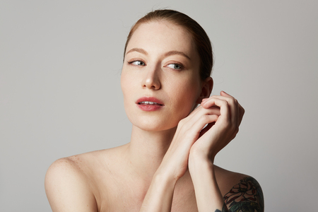 Handsome tattooed redhead female with bare shoulders holds her hand near the face over gray background. Cosmetology and skin care concept Stock Photo
