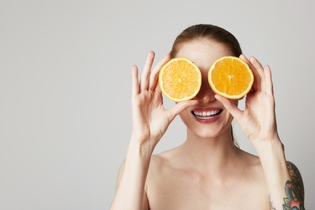 Happy cheerful tattoed young woman is holding two halves of an orange fruit in front of her eyes