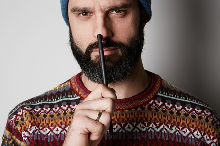 Portrait of Young thoughtful bearded man in blue beanie thinking about test over empty background Stock Photo