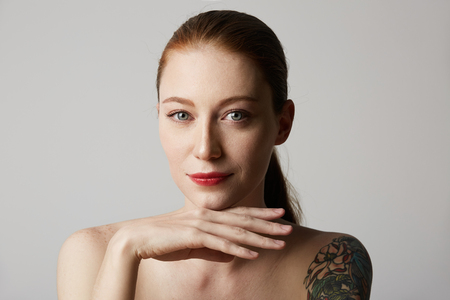 Cheerful tattooed redhead woman with bare shoulders holds her hand near the face over gray background. Cosmetology and skin care concept