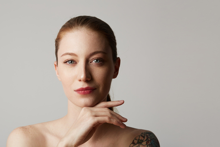 Beautiful tattooed redhead woman with bare shoulders holds her hand near the face over gray background. Cosmetology and skin care concept. Cope paste space.