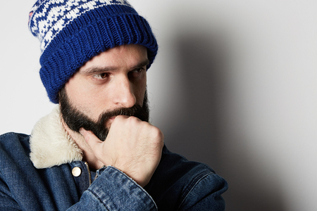 Pensive Bearded man Wearing blue jeans jacket and beanie on white background. Studio shot