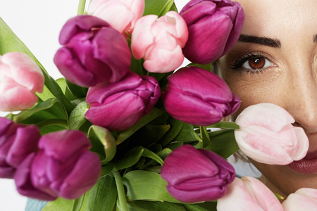 Beautiful girl with flowers tulips in hands on a light background. Closeup portrait. Stock Photo
