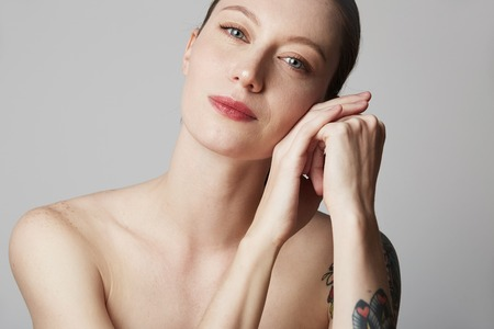 Cute tattooed redhead woman with bare shoulders holds her hand near the face over gray background. Cosmetology and skin care concept