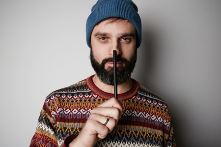 Handsome bearded man thinking with pen about ideas over white background Stock Photo