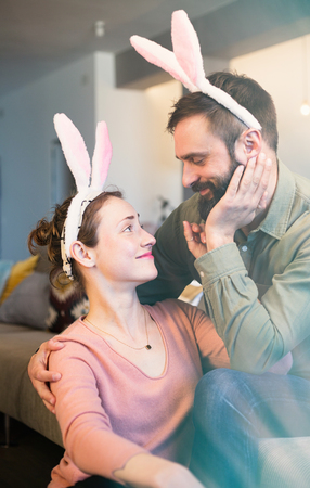 Beautiful young loving couple bonding to each other with pink rabbit ears on head. Happy family preparing for Easter. Vertical.