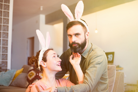 Beautiful young loving couple bonding to each other with pink rabbit ears on head. Happy family preparing for Easter Stock Photo