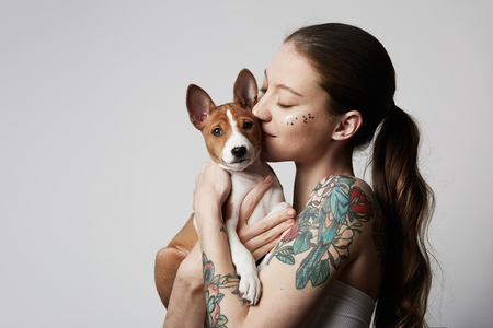 Portrait of a cute tattooed young woman hugging and kissing her little puppy basenji dog. Love between dog and owner. Isolated over white background