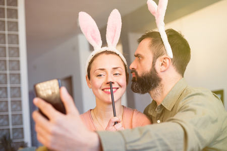 Young loving couple making selfie on mobile phone with pink rabbit ears on head. Happy family preparing for Easter. Flares