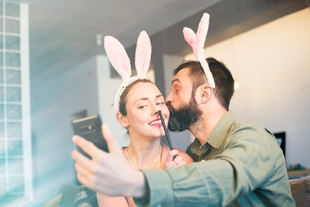 Young loving couple making selfie on mobile phone with pink rabbit ears on head. Happy family preparing for Easter