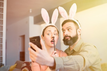 Young loving couple making selfie on mobile phone with pink rabbit ears on head. Happy family preparing for Easter. Flare.