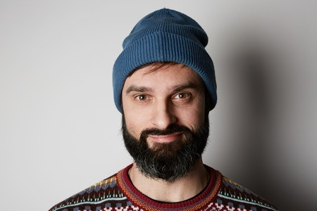 Bearded hipster wearing blue beanie and colored sweater on white background. Stock Photo