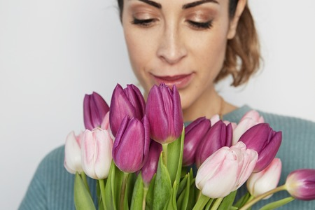 Portrait of a cheerful young girl holding pink tulips bouquet isolated over white background.