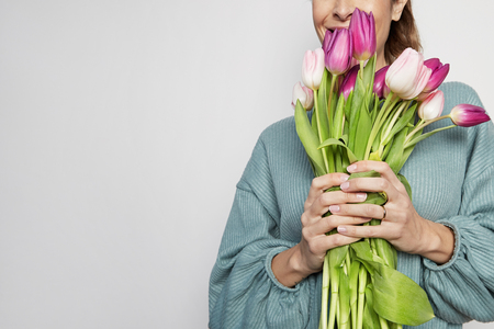 Portrait of a handsome young woman holding colored tulips bouquet isolated over gray background. Copy paste space. Stock Photo