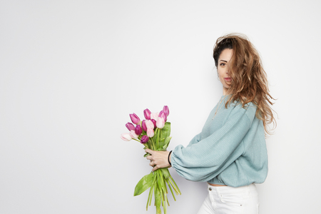 Portrait of a cheerful young woman holding colored tulips bouquet isolated over gray background. Copy paste space.