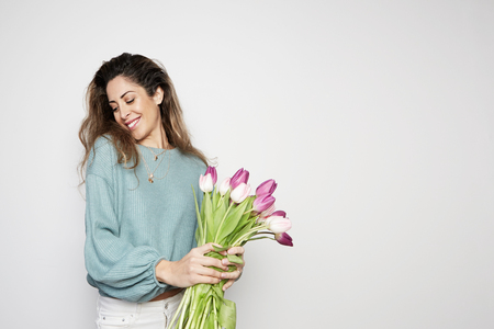 Portrait of a hppy young woman holding colored tulips bouquet isolated over gray background. Copy paste space.
