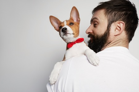 Handsome happy man snuggling and hugging his basenji puppy dog, close friendship against a white background Stock Photo