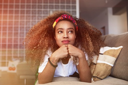 Closeup portrait of a happy young American African girl with long curly hair relaxing and have fun alone on sofa at modern home. Stock Photo