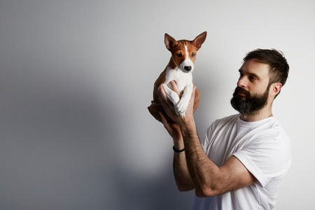 Happy bearded man with cute basenji puppy dog at home against a white background Stock Photo
