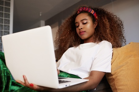 Young american african woman using laptop, texting friends via social networks. Student girl browsing Internet, using wi-fi, sitting on sofa at home