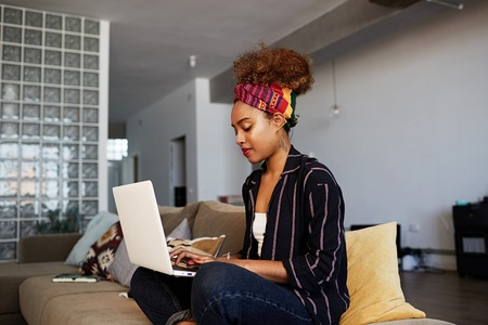 Young american african female blogger working remotely on digital netbook with internet text. African woman copywriter typing article for website on keyboard of modern laptop computer at home. Stock Photo