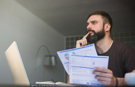 Bearded pensive man working at laptop and sitting at the table while looking at the papers and holding his head with hand.