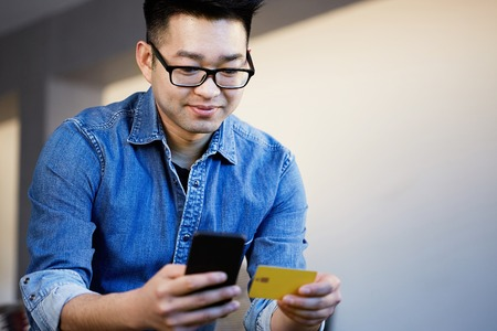 Young asian male holding hands credit card and mobile phone. Technology, internet banking, e-commerce and online shopping