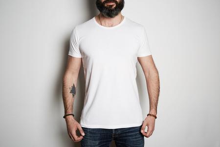 Un séduisant barbu tatoué brutal pose en jean bleu et un t-shirt gris vierge en coton d'été haut de gamme, sur une maquette de fond blanc.