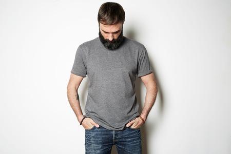 Bebaarde man in lege grijze t-shirt, witte muur op de achtergrond. Stockfoto