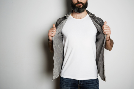 Positive brutal bearded male model poses in black jeans shirt and blank white t-shirt premium summer cotton, on white background