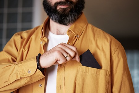 Bearded Businessman pulling out business card from pocket of his denim jacket, exchanging information with a potential partner. Mockup Copy Paste Blank Advertisement