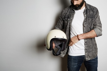 Stylish Brutal bearded male model poses in black jeans shirt and blank white t-shirt premium summer cotton with moto helmet in hands, on white background. Copy paste Advertisement 免版税图像