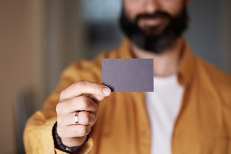 Bearded entrepreneur giving hand empty black business card on blurred background. Mockup Copy Paste Blank Advertisement 免版税图像