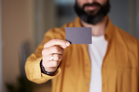 Bearded business man holding hand empty black business card on blurred background. Mockup Copy Paste Blank Advertisement 免版税图像