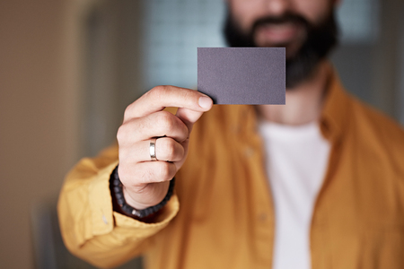 Bearded young man giving hand empty black business card on blurred background. Mockup Copy Paste Blank Advertisement