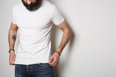 Un beau barbu tatoué brutal pose en jean bleu et un t-shirt gris vierge en coton d'été premium, sur fond blanc. Publicité Copier Coller Maquette