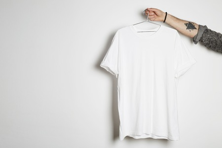 Tattooed hipster hand holds hang with blank white t-shirt from premium thin cotton on white background. Mockup Copy Paste Advertisement 免版税图像