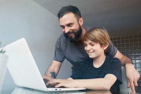 Cheerful young father with cute son using laptop computer while sitting on the table in the living room