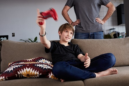 Handsome young boy playing video game console seated on a sofa while his father standing close in living room at home. 免版税图像