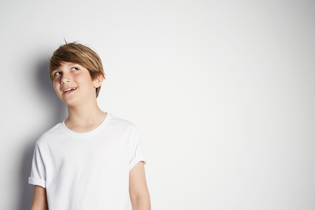 Handsome young boy in white T-shirt posing in front of white empty wall. Portrait of fashionable male child. Smiling boy posing, blank wall on background. Concept of children style and fashion