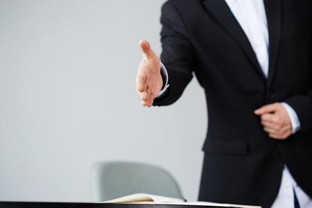 Selbstbewusster junger asiatischer Geschäftsmann, der nach Geschäftsabschluss Handschlag anbietet