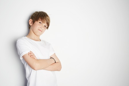 Cool young boy in white T-shirt posing in front of white empty wall. Portrait of fashionable male child. Smiling boy posing, blank wall on background. Concept of children style and fashion 免版税图像