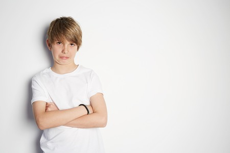 Upset young boy in white T-shirt posing in front of white empty wall. Portrait of fashionable male child. Smiling boy posing, blank wall on background. Concept of children style and fashion.