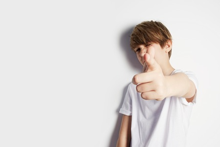 Attractive young boy in white T-shirt posing in front of white empty wall. Portrait of fashionable male child. Smiling boy posing, blank wall on background. Concept of children style and fashion