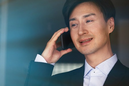 Confident asian businessman talking on mobile phone on blurred background. 免版税图像