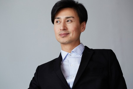 Portrait of confident asian businessman on empty background