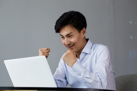 Happy excited young asian man with laptop at home sitting at the table. 免版税图像