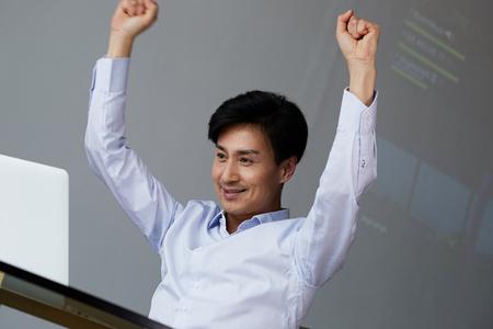 Happy Asian businessman raising his arm up when success, lifestyle concept.