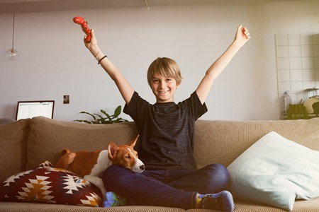 Handsome young boy celebrating his victory in video game console seated on a sofa with basenji dog puppy sleeping close in living room at home. 免版税图像