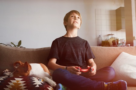 Handsome young boy playing video game console seated on a sofa with basenji dog puppy sleeping close in living room at home. 免版税图像